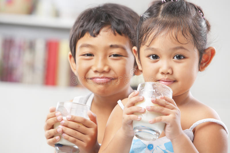 Due bambina e ragazzo ogni vetro della holding di latte immagine stock