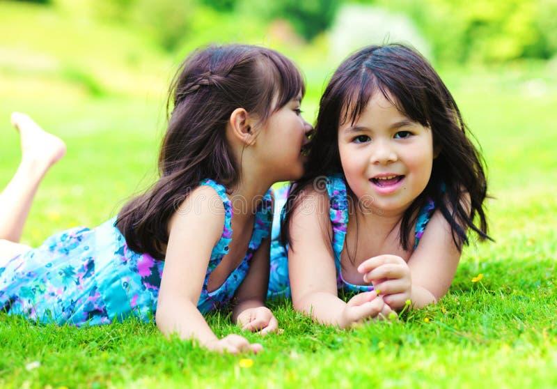 Due bambine che dicono un segreto fotografie stock libere da diritti
