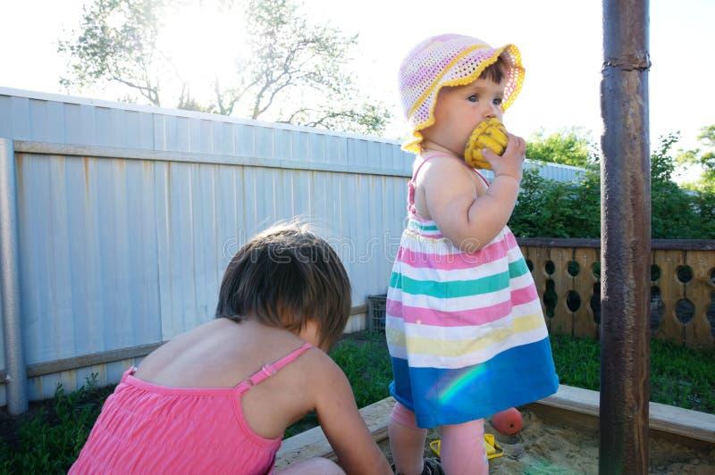 Due bambine che giocano in sabbiera Attività di estate per i bambini fotografia stock libera da diritti