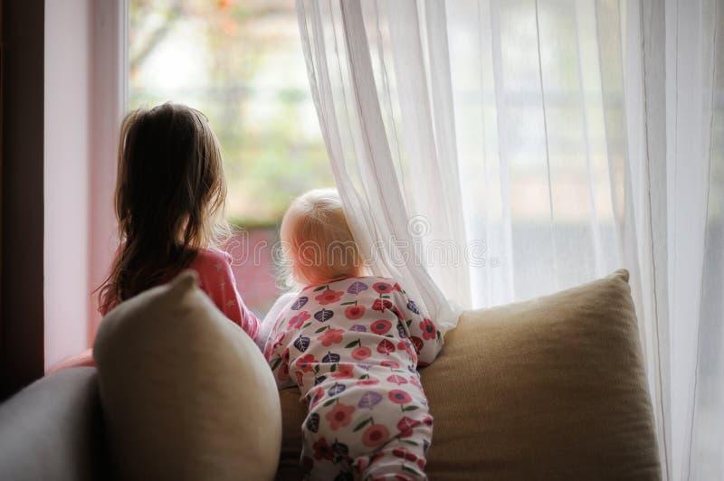 Due bambine che guardano dalla finestra fotografie stock