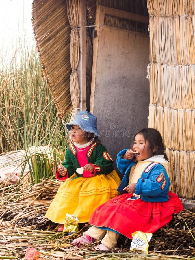 Due bambine che mangiano nel villaggio in Reed Islands su La immagini stock