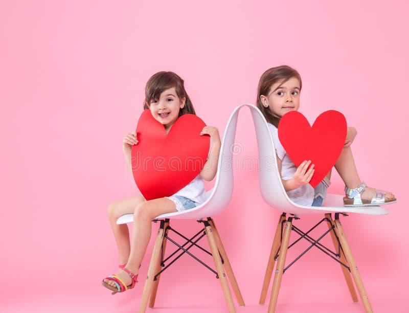 Due bambine con un cuore su un fondo colorato fotografia stock libera da diritti