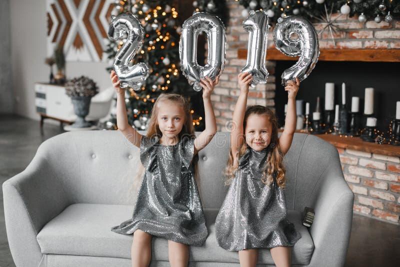 Due bambine di sorriso che si tengono per mano i palloni del nuovo anno, Numero 2019 Tempo di natale Concetto di nuovo anno fotografia stock libera da diritti