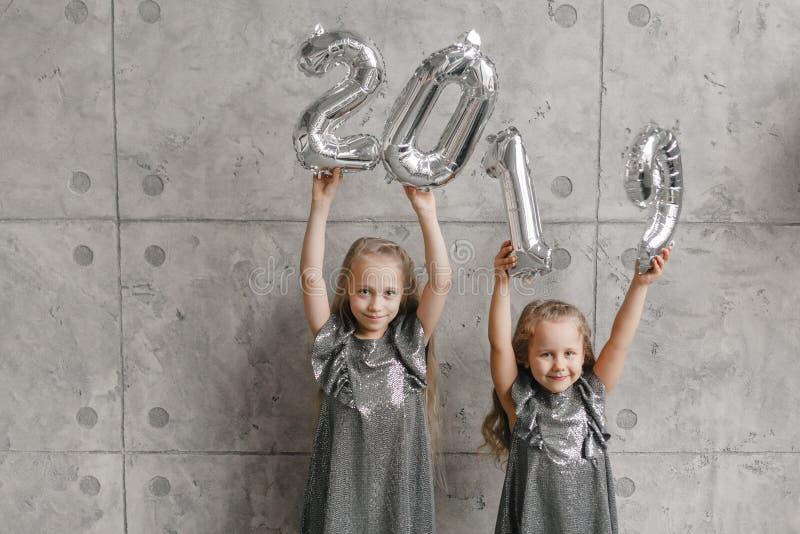 Due bambine di sorriso che si tengono per mano i palloni del nuovo anno, Numero 2019 Tempo di natale Concetto di nuovo anno immagini stock