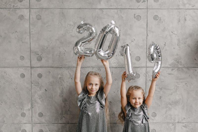 Due bambine felici che si tengono per mano i palloni del nuovo anno, Numero 2019 sul fondo grigio della parete Tempo di natale Nu immagine stock libera da diritti