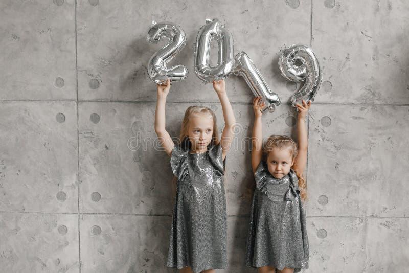 Due bambine offensive che si tengono per mano i palloni del nuovo anno, Numero 2019 Tempo di natale Concetto di nuovo anno immagini stock libere da diritti