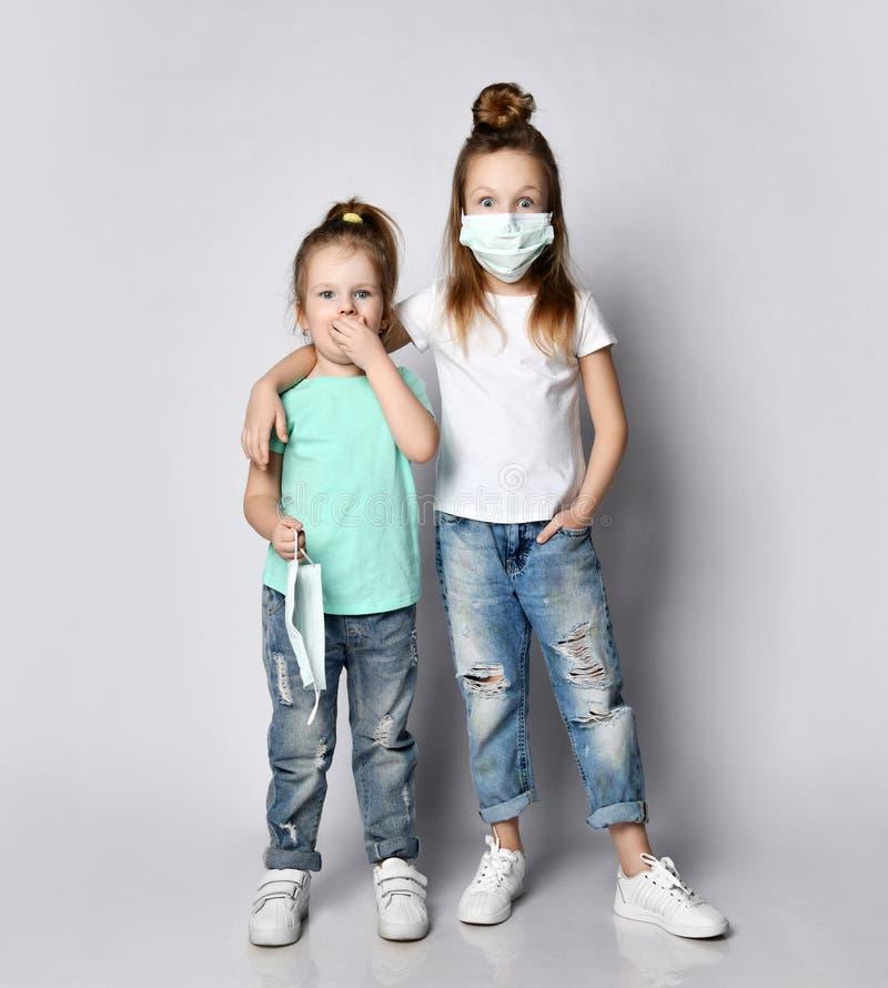 Due bambine spaventate, in maschere mediche del Coronavirus Covid-19, hanno paura della malattia fotografia stock