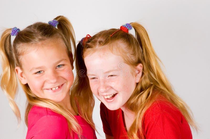 Due bambine stanno avendo molto divertimento fotografie stock