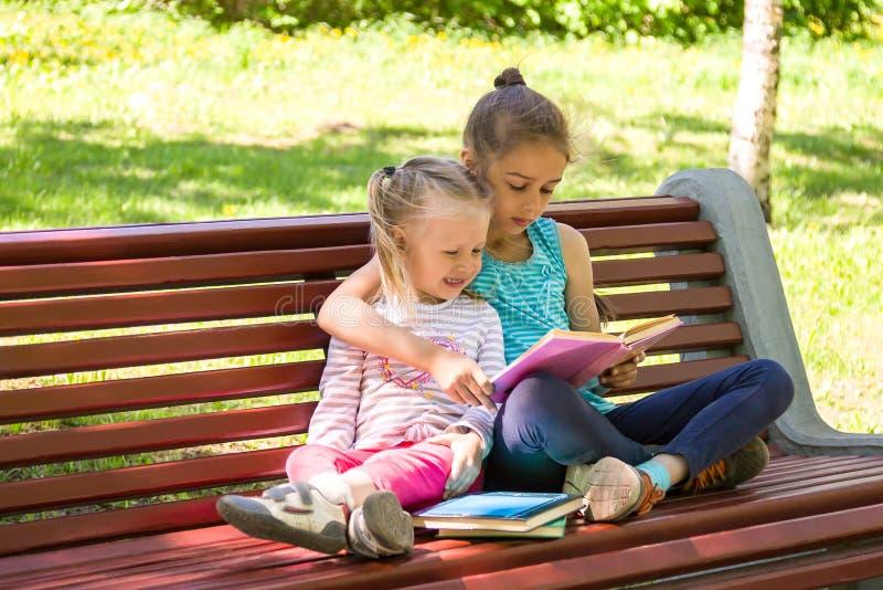 Due bambine stanno sedendo su un banco nel parco dell'estate e stanno leggendo un libro immagini stock