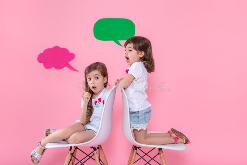 Due bambine su fondo colorato con le icone di discorso fotografia stock