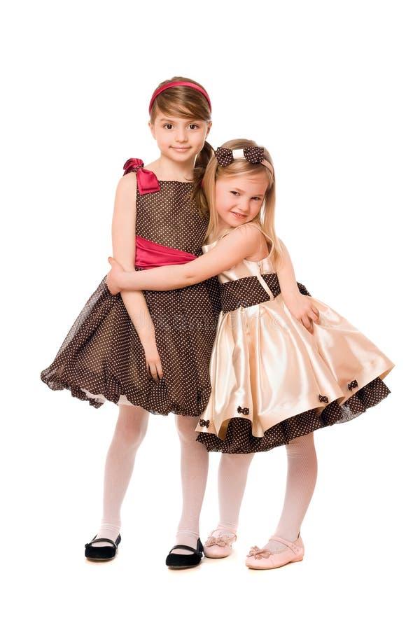 Due bambine sveglie in un vestito. Isolato fotografia stock libera da diritti