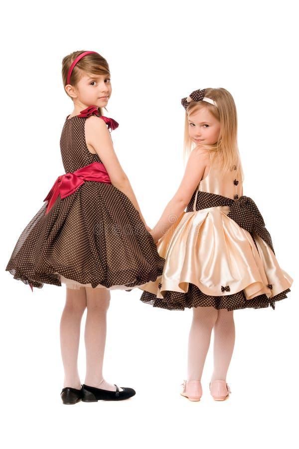 Due bambine in un vestito. Isolato immagini stock libere da diritti