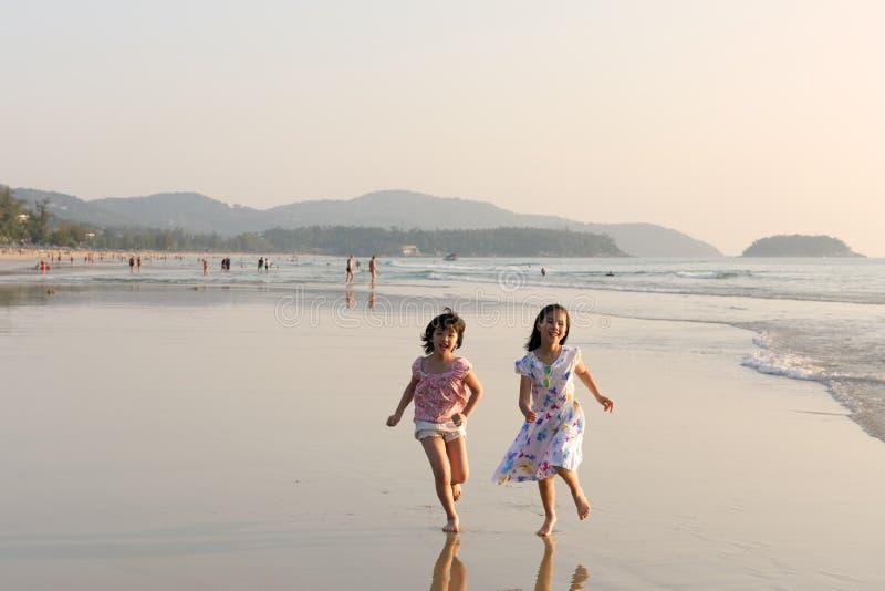 Due bambini asiatici che funzionano sulla spiaggia fotografia stock