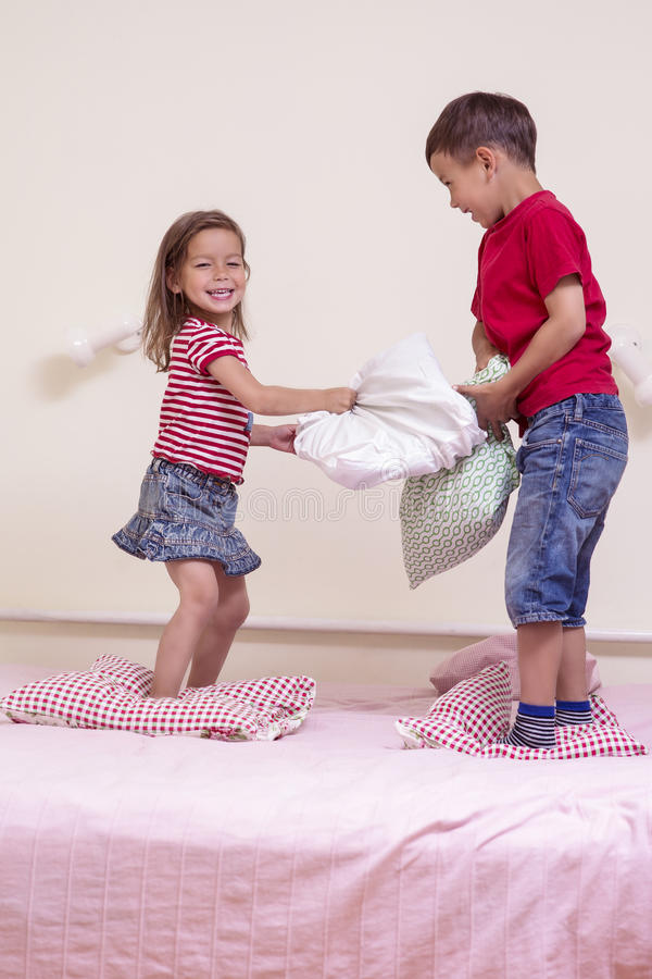 Due bambini caucasici che hanno una battaglia divertente del cuscino sul letto all'interno fotografia stock