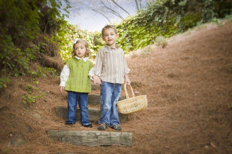 Due bambini che camminano giù i punti di legno con il canestro fuori. fotografia stock libera da diritti