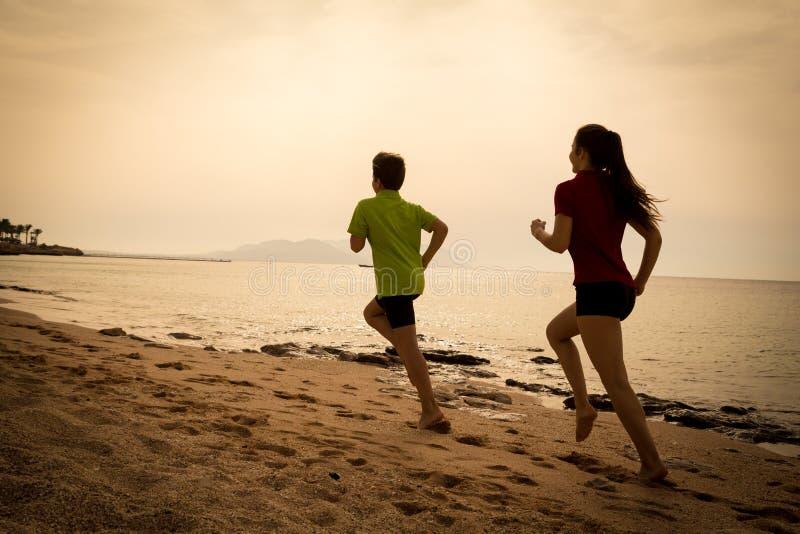 Due bambini che corrono insieme ai exersises di mattina, seppia tonificata immagini stock
