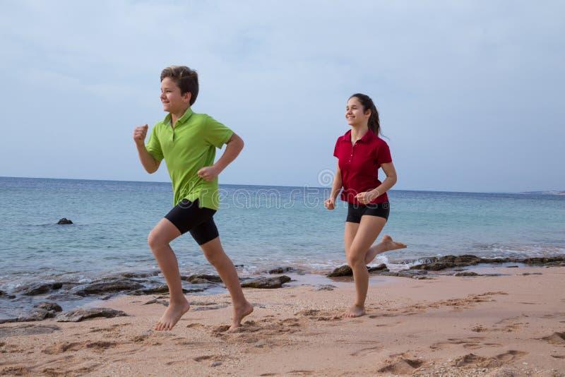 Due bambini che corrono insieme ai exersises di mattina immagini stock libere da diritti