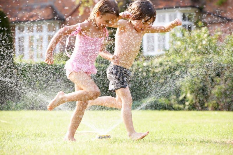 Due bambini che funzionano tramite lo spruzzatore del giardino fotografia stock libera da diritti