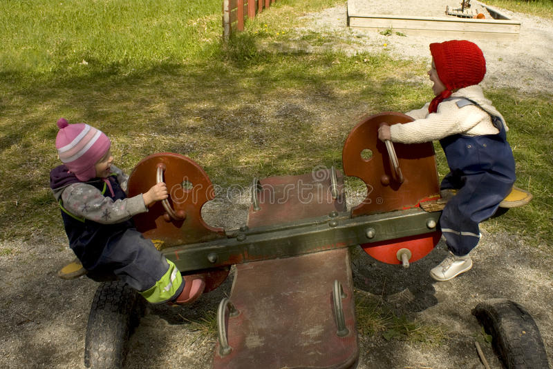 Due bambini che giocano su un totter della bascula immagine stock libera da diritti