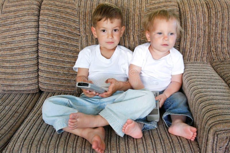 Due bambini che guardano TV fotografia stock