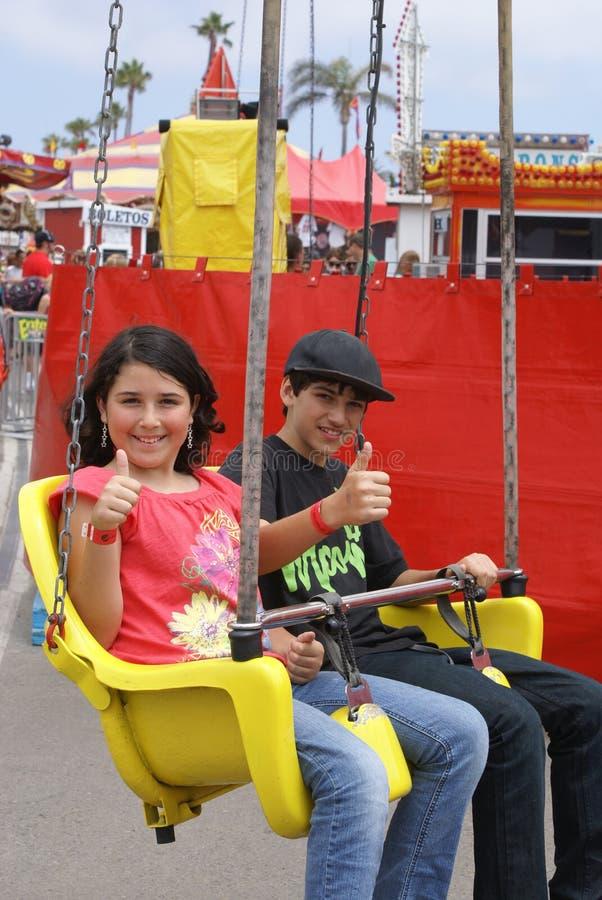 Due bambini che guidano un giro alla fiera o al carnevale fotografia stock