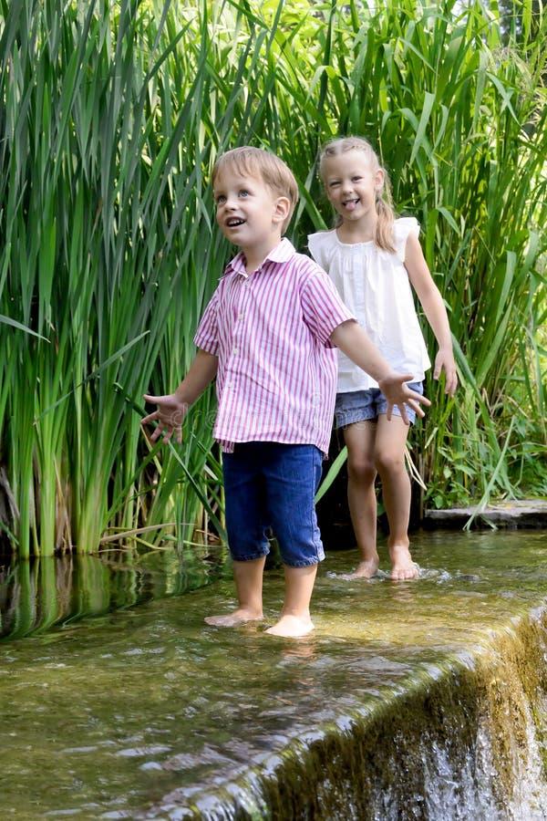 Due bambini che hanno buona estate diverta con la cascata fotografia stock