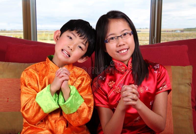 Due bambini che offrono i saluti cinesi del nuovo anno immagini stock
