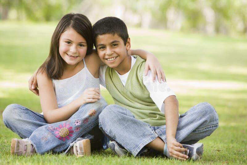 Due bambini che si siedono nella sosta immagine stock libera da diritti