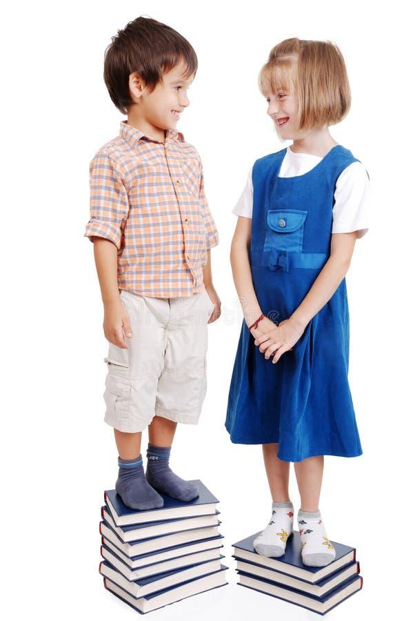 Due bambini che stanno sui libri immagine stock