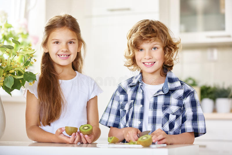 Due bambini che tagliano un kiwi immagine stock libera da diritti