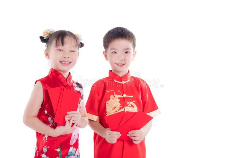 Due bambini cinesi in costume tradizionale che tiene i soldi rossi del pacchetto sopra bianco fotografia stock libera da diritti
