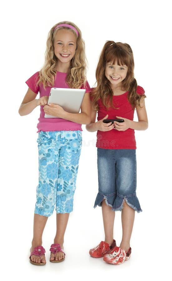 Due bambini con i dispositivi fotografia stock libera da diritti