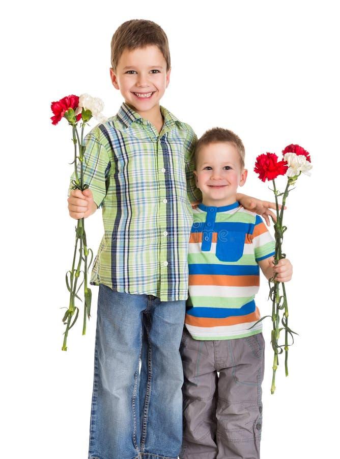 Due bambini con i garofani fotografie stock