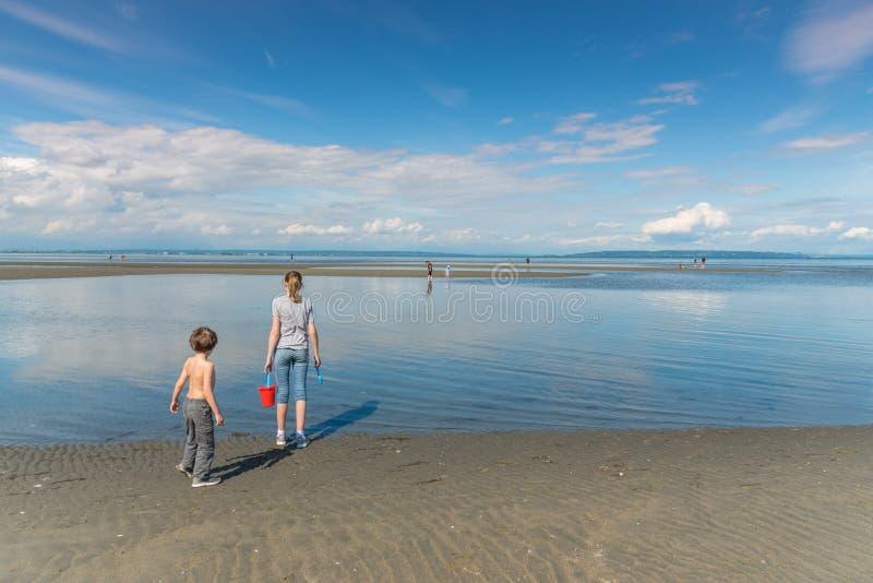 Due bambini con il secchio della sabbia che sta alla spiaggia centennale alla bassa marea fotografia stock