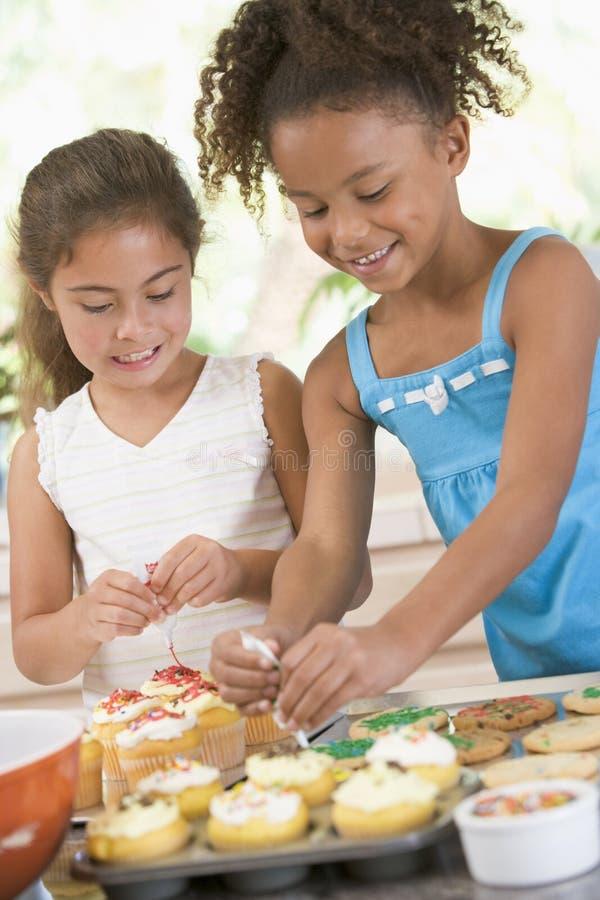 Due bambini in cucina che decorano i biscotti fotografia stock libera da diritti