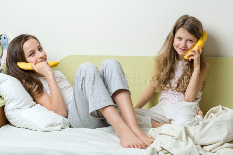 Due bambini della sorella in pigiami, banane come telefoni immagine stock libera da diritti