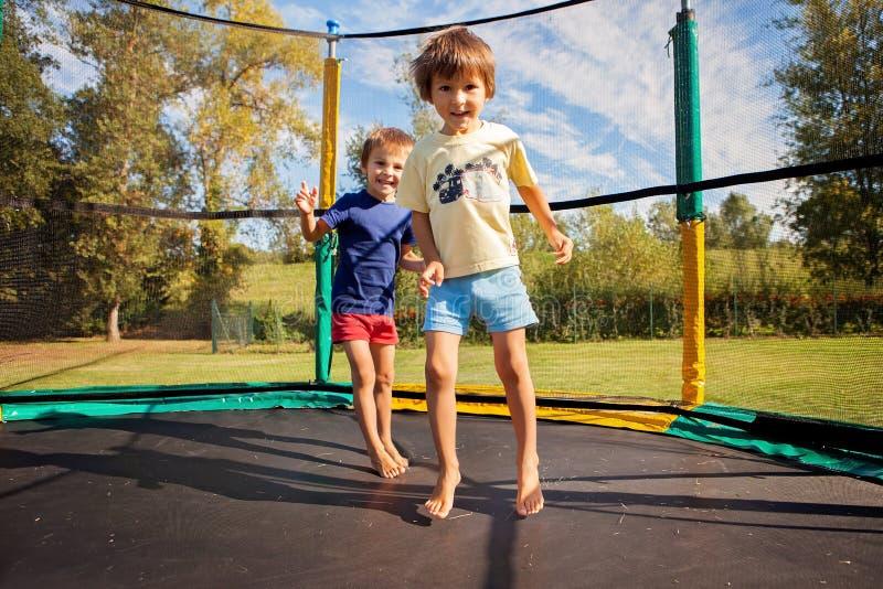 Due bambini dolci, fratelli, saltanti su un trampolino, estate, h fotografia stock libera da diritti