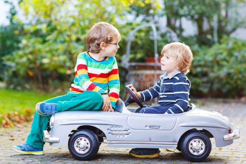 Due bambini felici che giocano con la grande vecchia automobile del giocattolo di estate fanno il giardinaggio, ou fotografie stock libere da diritti