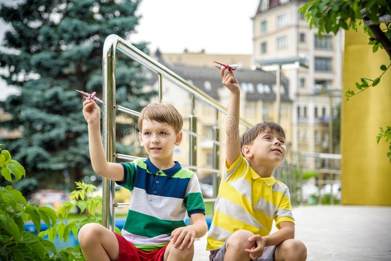 Due bambini felici del fratello che giocano con l'aeroplano del giocattolo il giorno di estate caldo I ragazzi esaminano la copia fotografia stock libera da diritti