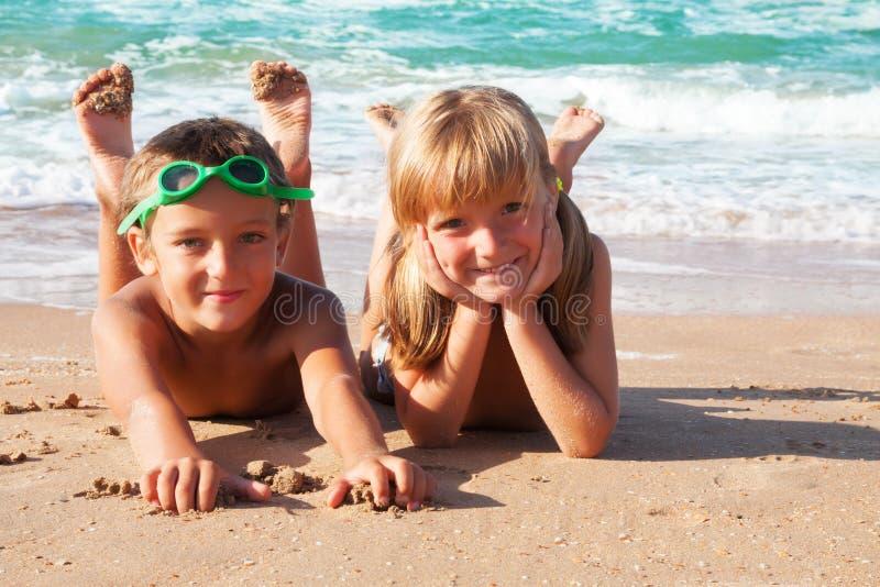 Due bambini felici sulla spiaggia, mare nel fondo. immagine stock