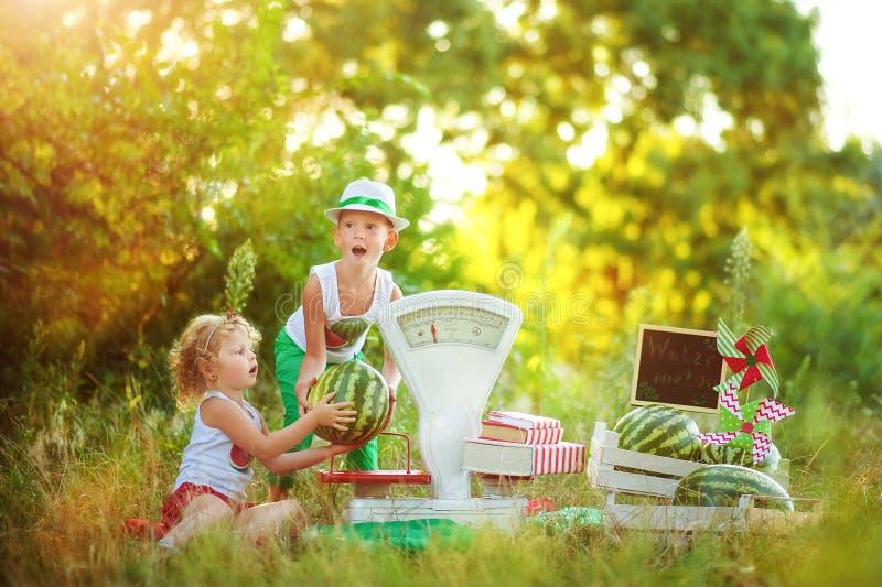 Due bambini fratelli e sorelle giocano con i venditori di cocomeri a biliardino con scale bianche di vecchia moda Ragazza e ragaz fotografie stock