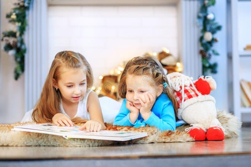 Due bambini hanno letto un libro Due sorelle Nuovo anno di concetto, Chris allegro fotografie stock libere da diritti