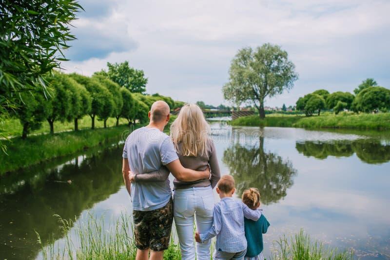 Due bambini, madre e padre considerare lago nella vista posteriore di giorno di estate immagini stock