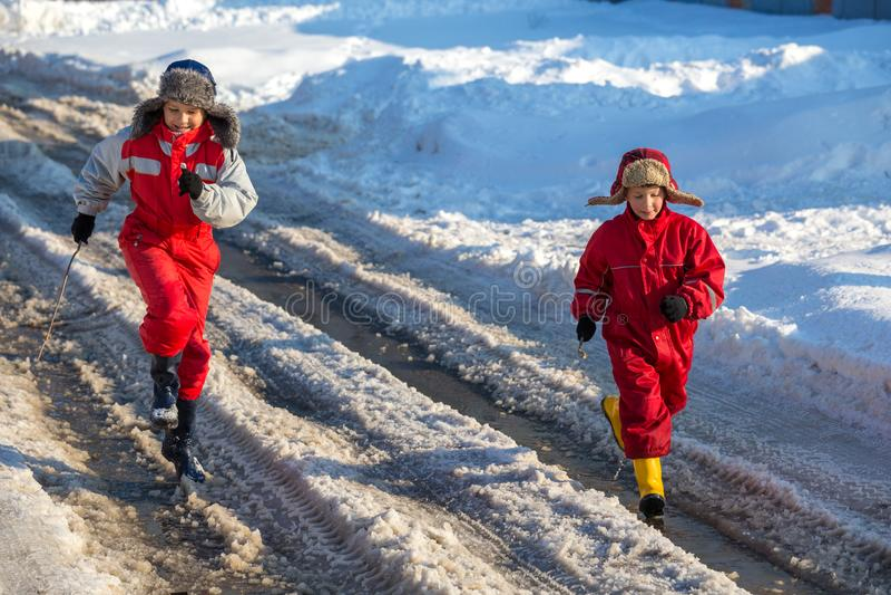 Due bambini nei rainboots che corrono sul ghiaccio sguazzano fotografia stock libera da diritti