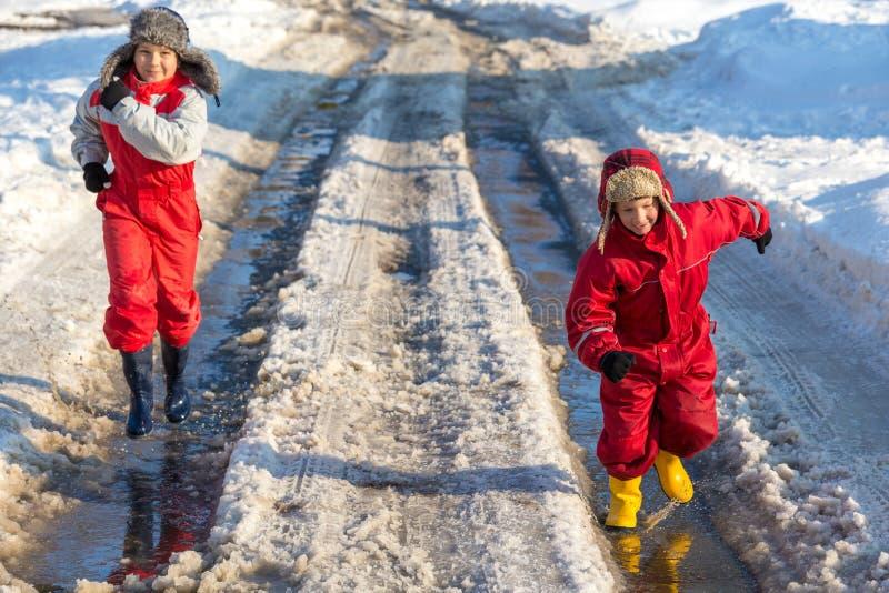 Due bambini nei rainboots che corrono sul ghiaccio sguazzano fotografie stock