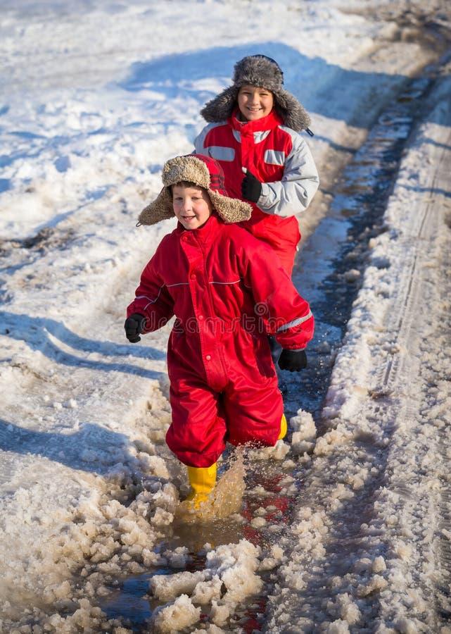 Due bambini nei rainboots che corrono sul ghiaccio sguazzano immagine stock