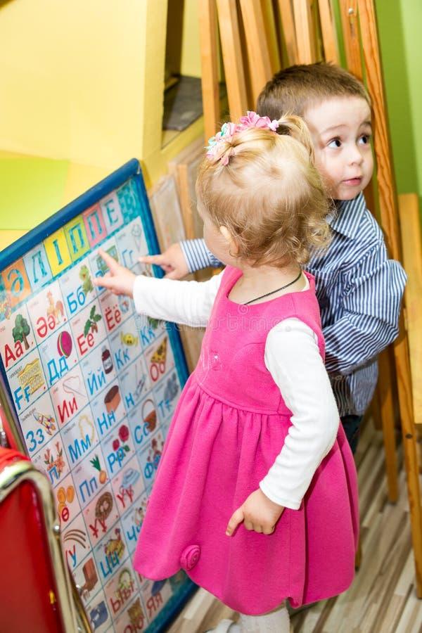 Due bambini nella classe della scuola materna di Montessori Gioco del ragazzo e della bambina fotografia stock