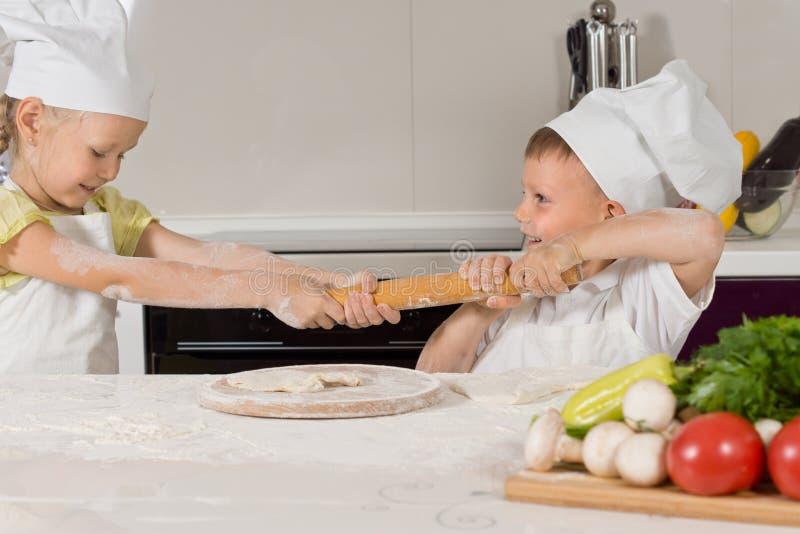 Due bambini piccoli che combattono sopra un matterello fotografia stock libera da diritti