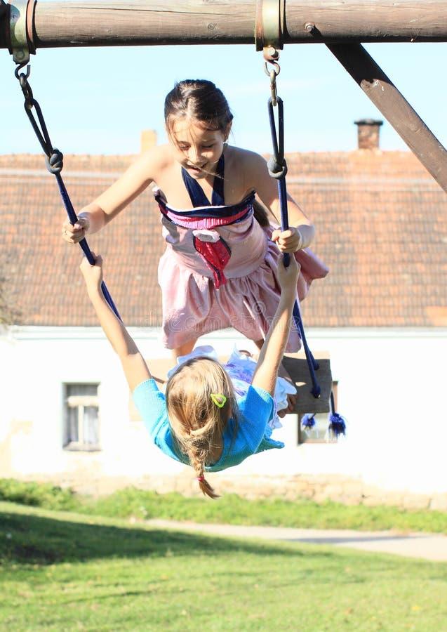 Due bambini - ragazze che oscillano sull'oscillazione immagine stock
