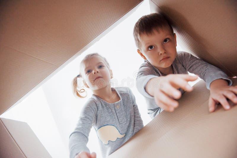 Due bambini ragazzo e scatola di cartone di apertura della ragazza e guardare dentro con la sorpresa immagini stock libere da diritti